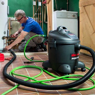 a plumber using a Shop-Vac Pump Vac wet and dry vacuum cleaner